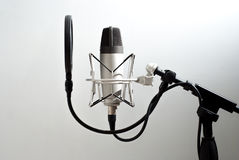 Microphone stand on wall background. Voice recording. On the air. Stock Photos