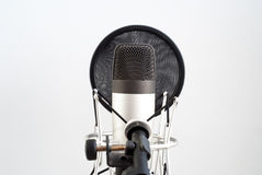 Microphone stand on wall background. Voice recording. On the air. Stock Image