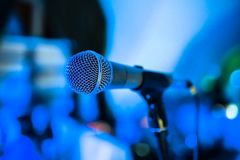 Microphone stands on stage in a nightclub. Bright club light shines on MIC. Performances in the night club royalty free stock photography