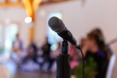 Microphone on a straight stand, with blurry specialists giving a conference royalty free stock photography