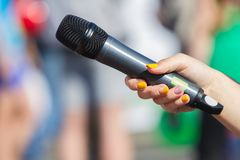 Microphone in a street interview. Microphone in hand close up in a street interview royalty free stock photography