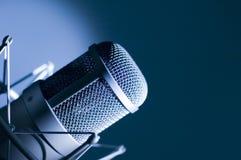 Microphone in studio. Dark blue light Stock Photo