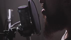 A microphone in the studio, a man appears, starts reciting or humming. 4K Slow Mo