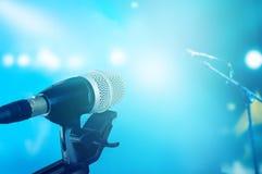 Microphone sur l'étape avec le concert vibrant bleu d'éclairage Images libres de droits