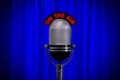 Microphone sur l'étape avec le projecteur sur le rideau bleu Photographie stock libre de droits