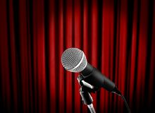 Microphone sur l'étape avec le rideau rouge photographie stock