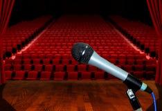 Microphone sur l'étape avec les sièges vides d'amphithéâtre Photo libre de droits