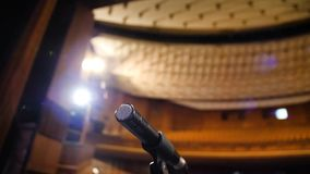 Microphone sur l'étape et hall vide pendant la répétition Microphone sur l'étape avec des étape-lumières à l'arrière-plan Photos stock