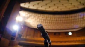 Microphone sur l'étape et hall vide pendant la répétition Microphone sur l'étape avec des étape-lumières à l'arrière-plan Photo libre de droits