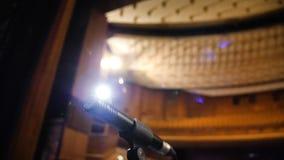 Microphone sur l'étape et hall vide pendant la répétition Microphone sur l'étape avec des étape-lumières à l'arrière-plan Images stock