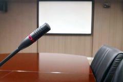 Microphone sur le bureau en bois dans l'esprit de salle de conférence ou de lieu de réunion photos libres de droits
