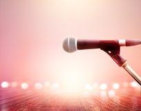 Microphone sur le concert vibrant d'éclairage, fond en bois de plancher photos stock
