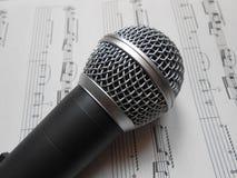 Microphone sur les notes de musique photographie stock