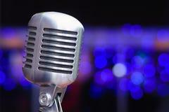 Microphone sur un fond des lumières bleues Photographie stock libre de droits