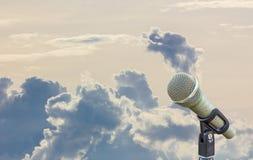 Microphone sur un support avec le grand nuage gris brouillé dans le backgro Image stock