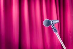 Microphone sur un support avec le rideau rouge brouillé, copyspace sur Photos libres de droits