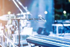 Microphone and synthesizer on stage. Microphone and synthesizer on concert stage with defused bokeh lights blue colour background royalty free stock image
