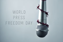 Microphone and text world press freedom day. Closeup of a microphone encircled by a red barbed wire and the text world press freedom day on a gradient gray Royalty Free Stock Images