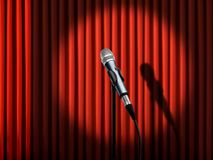 Microphone under spotlight. Over red curtains Royalty Free Stock Images