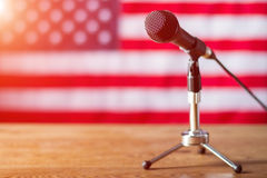 Microphone on US flag background. Table with microphone and banner. Radio show about to begin. Good morning, fellow citizens royalty free stock images