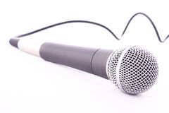 Microphone on white. A microphone isolated on a white background with cable trailing off in the background stock photos