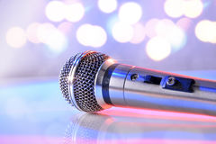 Microphone on white crystal table and pastel bokeh background. Microphone reflected on white crystal table and pastel bokeh background. Front view. Horizontal stock photos