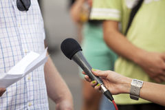 Microphone in woman's hand. TV or radio reporter interview Royalty Free Stock Image