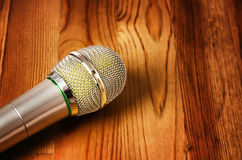 Microphone on wooden background stock image