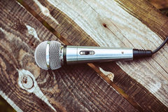 The microphone is on wooden boards. Silver microphone on wooden boards. View from above Royalty Free Stock Photo