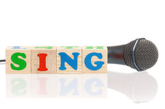 Microphone and word Sing. Isolated on white background Royalty Free Stock Photo
