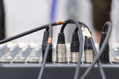 Microphone xrl connectors pluged in a audio mixing console. Copx space Royalty Free Stock Photos