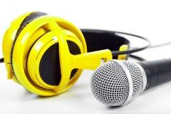 Microphone and yellow headphones Stock Photos