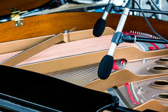 Microphones above the strings of black grand piano with raised l Royalty Free Stock Image