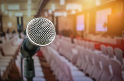 Microphones on abstract blurred of speech in seminar room or fro. Nt speaking conference hall light, white chairs for people in event meeting convention hall in stock photos