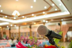 Microphones on abstract blurred of speech in seminar room or front speaking conference hall light, white chairs for people in. Event meeting convention hall in royalty free stock images