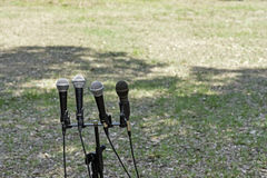 Microphones against grass background Stock Photography