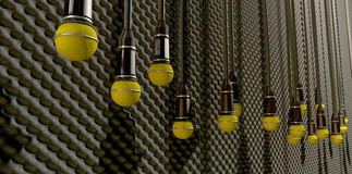 Microphones Dangling On Sound Proof Acoustic Foam. A front view of a row of yellow microphones dangling by cords at various heights on a grey acoustic foam wall Stock Photos