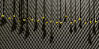 Microphones Dangling On Sound Proof Acoustic Foam. A front view of a row of yellow microphones dangling by cords at various heights on a grey acoustic foam wall Royalty Free Stock Photography