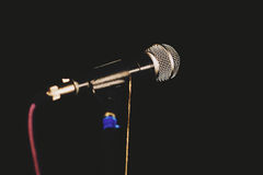 Microphones in the darkness. Shining vocal microphone with stand and cable with shadows on black background stock image