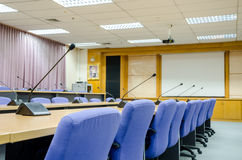 The microphones in front of empty chairs in meeting room. Stock Images
