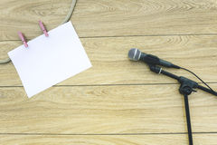 Microphones on lyric background. Microphone on the stand and a sheet of paper on clothespins on a wooden background Royalty Free Stock Photography