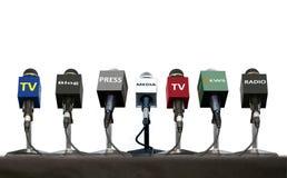 Microphones pendant l'entrevue de presse sur une table au-dessus de blanc Photo libre de droits