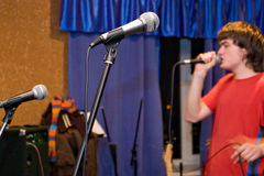 Microphones and singer. Microphones on foreground and singer in red t-shirt on background Stock Photo