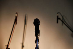 Microphones on the stage. Vocal microphone and two blurred studio recording microphones with shadows against highlighted background royalty free stock image