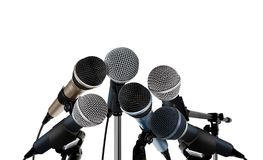 Microphones Standing over White. Image of Microphones Standing over White Stock Photo