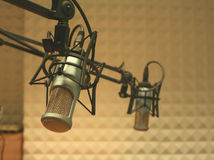 Microphones in a studio. Two microphones in a radio studio, acoustic foam in the background royalty free stock photo