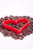 Microplaqueta de chocolate com os cortadores vermelhos do coração Fotografia de Stock Royalty Free