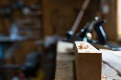Microplaqueta de madeira no foco, placa do pinho, worbench do carvalho, ferramentas da carpintaria no fundo blurried fotografia de stock