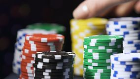 Microplaquetas coloridas do casino que gerenciem ao redor, mão fêmea que toma alguns símbolos para fazer a aposta vídeos de arquivo