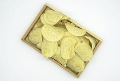 Microplaquetas de batata amarelas fritadas na bandeja de madeira isolada no fundo branco do arquivo com trajeto de grampeamento Fotos de Stock Royalty Free